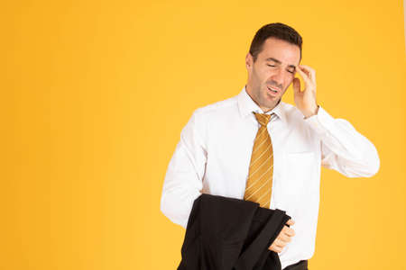 Portrait of businessman feeling stressed and tiring on yellow background.
