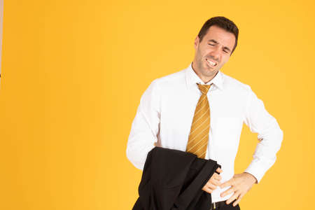 Portrait of businessman feeling bored on yellow background.
