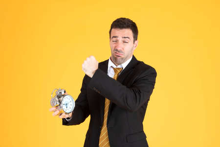 Portrait of a handsome businessman holding clock feeling tired on yellow background. 免版税图像