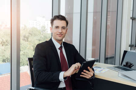 Young businessman is sitting in the office while using tablet to research some information. Reklamní fotografie