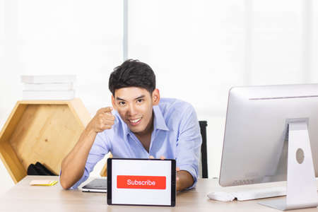 Young Asian influencer holding a table with subscribe sign while recording a video. Stock Photo