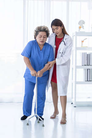Young attractive Asian doctor is helping an old patient walking, hospital and healthcare concept.