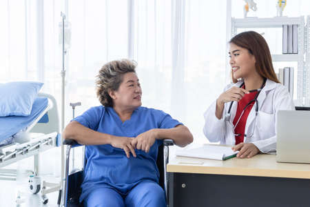 Young attractive Asian doctor is discussing to the patient about her symptoms, healthcare and hospital concept.