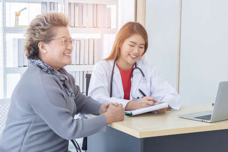 Asian doctor working in the office and discussing  to the patient about her symptoms, healthcare and hospital concept.