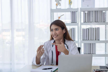 Young Asian doctor working on her desk, holding medicine, hospital and healthcare concept.