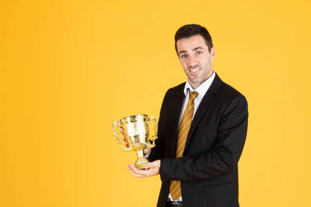 Portrait of a handsome businessman wearing white suit and tie while holding a golden trophy with yellow background.