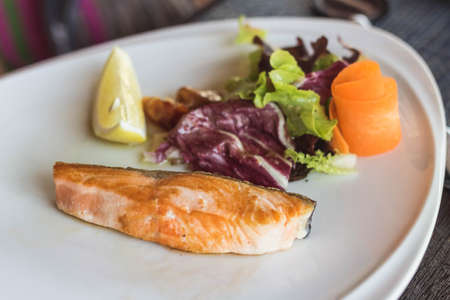 Salmon grilled on the white plate, serve with vegetables and lemon.