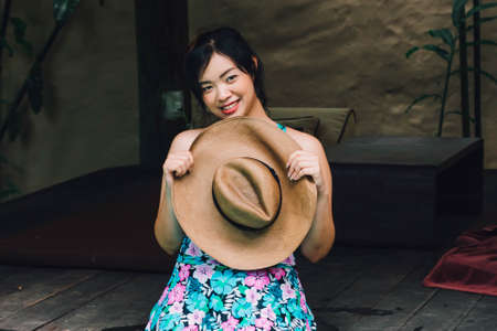 Young Asian woman relaxing at the pool, holding straw hat.