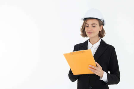 Portrait of a woman in hard hat and suit looking at camera while standing and holding clipboard with documents isolated over white background. Stock fotó