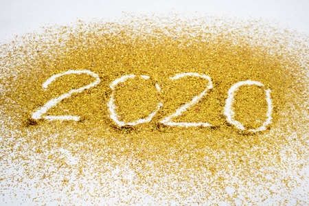 2020, text of gold glitter on the white background. 免版税图像
