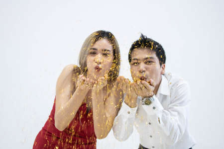 close up of young Asian couple blowing confetti together with white background.
