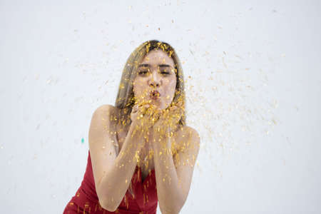 close up of young Asian woman blowing confetti  with white background.