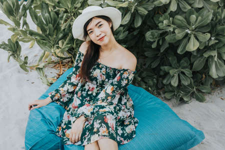 Young Asian woman in green floral dress sitting on the blue pillow at the beach, wearing beach hat, travel concept.