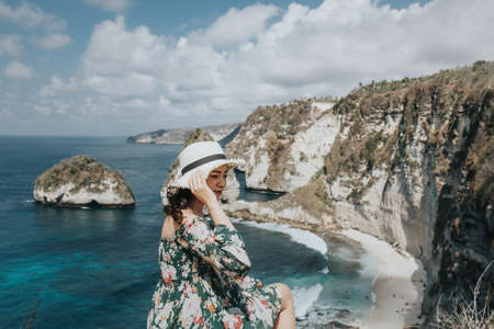 Young pretty Asian woman feeling relax with mountain view at Diamond beach in Bali. Stock fotó