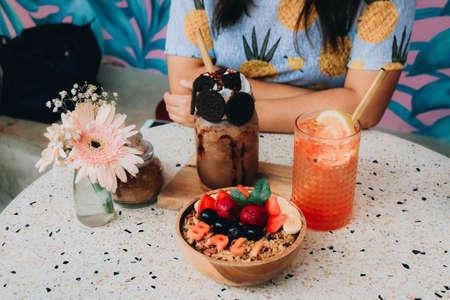 Healthy breakfast bowl with fresh berries, nuts, bananas and chocolate smoothie drink. Vegan food.