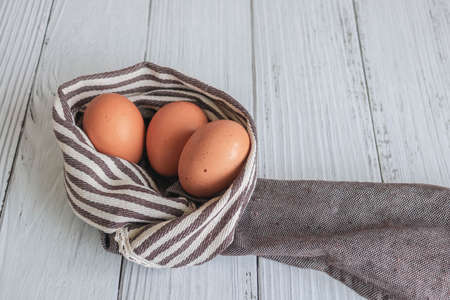 Brown chicken eggs lay on the wooden floor with brown fabric, vintage style.