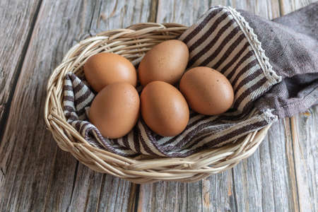 Brown chicken eggs in the wooden basket with cute fabric, close-up view. Banque d'images