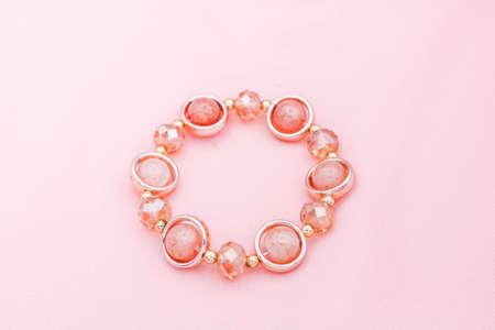 Pink beads bracelet on pink background. Banque d'images