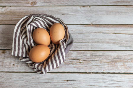 Brown chicken eggs lay on the wooden floor with brown fabric. Banque d'images