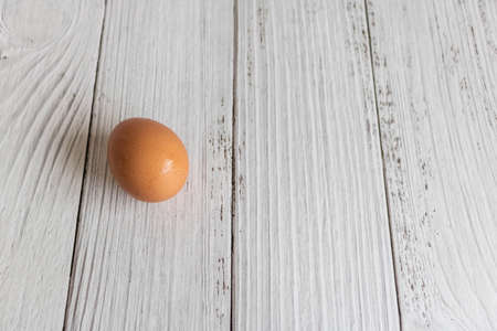 Brown chicken eggs lay on the wooden floor.