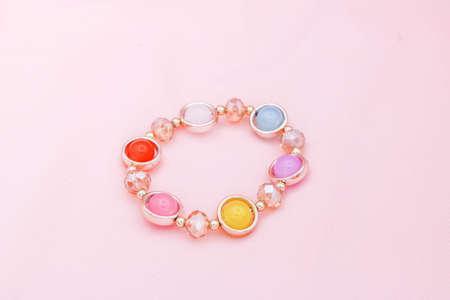Colorful beads bracelet on pink background.