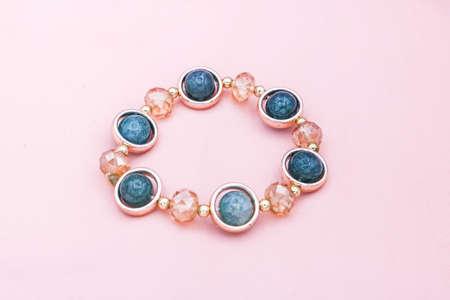 Blue beads bracelet on pink background. Banque d'images