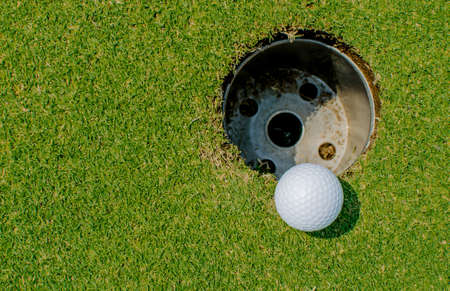 Golf ball very close to the hole photo