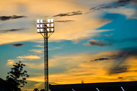 football field: Pillar spotlights football field in the background blue sky at sunset  Stock Photo