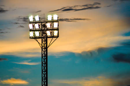 Pillar spotlights football field in the background blue sky at sunset  Stock Photo