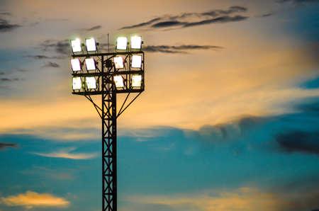 Pillar spotlights football field in the background blue sky at sunset  Imagens