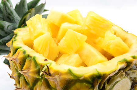 Cubed pineapple presented in its own bowl on white background
