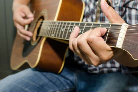 fingering: Acoustic guitar being played, Fingers holding a chord.
