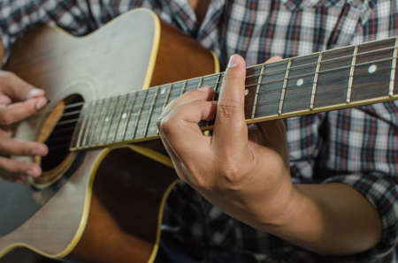 fingerboard: Acoustic guitar being played, Fingers holding a chord.