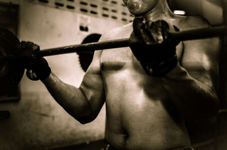 Young guy with muscular body with barbell over, dramatic Stock Photo
