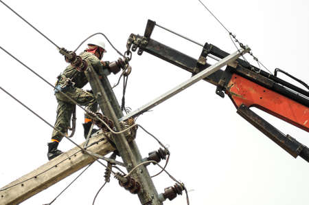custodian: Electrician lineman repairman worker at climbing work on electric post power pole
