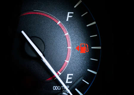 Fuel Gauge Showing Almost Empty,Time for another very expensive fuel purchase. Red warning icon light door. Stock Photo