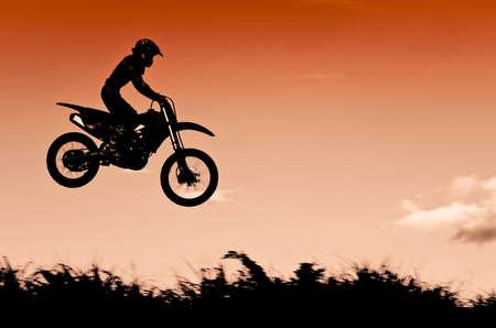 motorized sport: Status of silhouate motocross jumping over the amber light of sunset background.