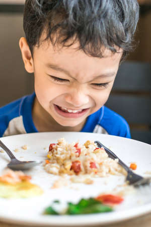 Angry Asiatic kid with breakfast, bored with food photo