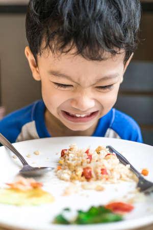 ni�os tristes: Chico asi�tico enojado con el desayuno, aburrido de la comida