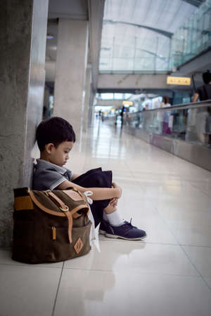 Depressed young boy sitting alone in a hallway photo