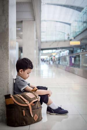 forlorn: Depressed young boy sitting alone in a hallway