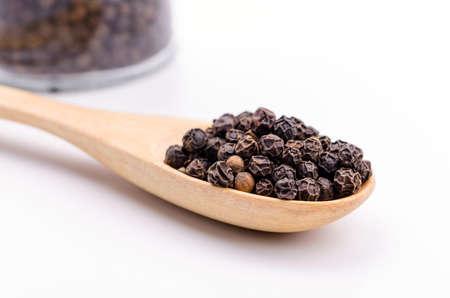 pepe nero: Pepe nero in cucchiaio di legno su sfondo bianco.