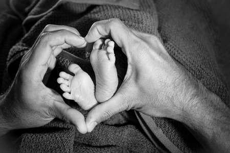 papa y mama: Pies del beb� en las manos del padre, coraz�n Foto de archivo