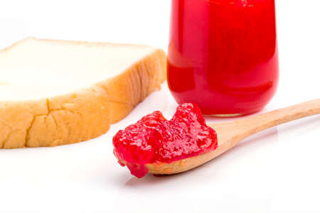 whole wheat bread with strawberry jam on white background. photo
