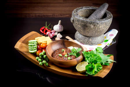 Thai cuisine nam prik or chili paste mixes with fish serves with various vegetables Imagens