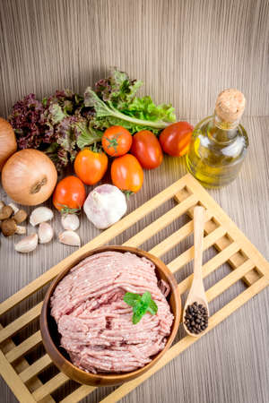 fatness: Raw ground meat in wood bowl. Minced pork on a background of fresh organic vegetables