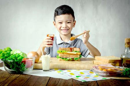 bocadillo: Little Boy Haciendo un emparedado en cocina Foto de archivo