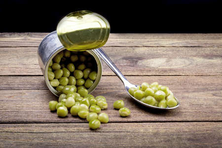 vegetable tin: Canned Peas on vintage wooden background