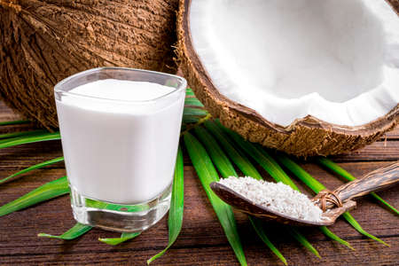 Coconut and coconut milk in glass on wooden table Imagens