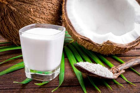mleka: Kokosowe i mleko kokosowe w szklanych na drewnianym stole
